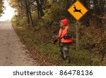 hunter standing by a deer crossing sign waiting for game - stock photo