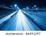 rush hour traffic at night, light trails on the fast lane - stock photo