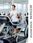man at the gym doing exercise on the treadmill - stock photo