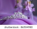 Close-up photo of the silver or platinum (white gold) diadem with diamonds on a lilac background. In the background is purple fabric and decoration of flowers. Tiara for the bride. - stock photo