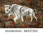 An old rock art drawing of a white buffalo painted on a rocky outcrop. - stock photo