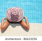 Woman enjoying sun in swimming pool - stock photo