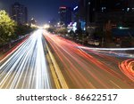 light trails on rush hour traffic at night in beijing,China - stock photo