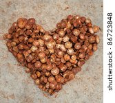 Pile of Dried Betel Nut in heart shape isolated on a texture background. - stock photo