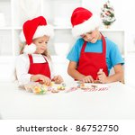 Kids decorating christmas cookies in the kitchen - stock photo