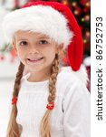 Happy girl portrait in front of the christmas tree - closeup - stock photo