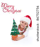 Happy christmas girl in santa hat holding potted fir tree decoration - stock photo