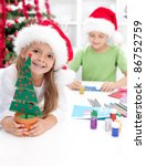 Happy kids making christmas decorations and postcards - stock photo