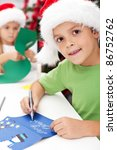 Kids making and writing christmas greeting cards in holidays season - closeup - stock photo