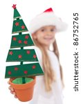 Christmas tree decoration in happy little girl hand - isolated, shallow depth - stock photo
