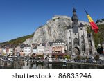 The center of the town of Dinant with the citadelle on the rock and Collegiate Church of Notre-Dame  at the Meuse river, with a Belgian flag on the right. - stock photo