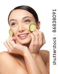 Close-up face of beautiful woman with clean fresh healthy skin and with cucumber slices around the cheeks. Isolated on white - stock photo