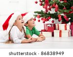Happy kids laying on the floor in front of the christmas tree - stock photo