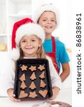 Christmas gingerbread cookies are ready - happy kids in the kitchen - stock photo