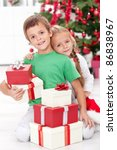 Loving siblings with lots of presents at christmas time - stock photo