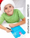 Happy kid writing handmade decorated letter to santa - stock photo