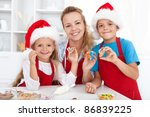 Happy family making and decorating christmas cookies - stock photo