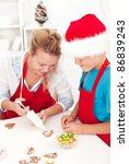 Woman and child making decorated christmas cookies - stock photo