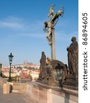 Statue of Jesus on Charles Bridge - Prague Castle in Background, Czech Republic - stock photo