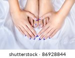 body part shot of beautiful healthy young woman's hands and legs with manicured fingers and pedicured toes on silk cloth - stock photo