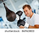 Male boxer at the gym hitting the punching ball - stock photo