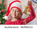 little girl with christmas bell and spruce tree - stock photo