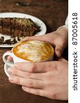 Closeup of female hands holding cup of Cappuccino - stock photo