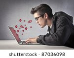 Young man using a laptop with red bubbles coming out of its screen - stock photo