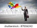 Businessman spraying colored paint with cityscape in the background - stock photo