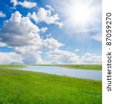 green grass with river under sun - stock photo