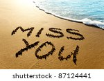"Small photo of Dramatic inscription ""Miss You"" on wet golden beach sand in sunset light"