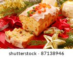 traditional christmas cake  (keks ) with dried fruits,jelly and icing on red plate - stock photo