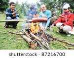 Barbecue in nature, group of people preparing sausages on fire (note: shallow dof) - stock photo