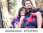 Happy couple sitting together outdoors during hiking travel. Interracial active couple. - stock photo