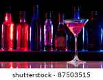 Stock photo cocktail glass with drink in the bar with bottles in the dark background 87503515