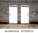 Two white doors on brick wall illustrating choices - stock photo