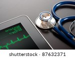 Doctor workplace with tablet display electrocardiogram (ECG) and stethoscope - stock photo
