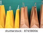 paper Shopping yellow gift bags on green background ecologocal - stock photo