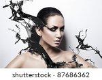 close up portrait of passion brunette woman with black splash - stock photo