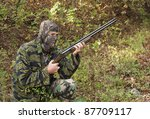 camouflaged hunter with a rifle kneeling in the woods - stock photo