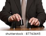 Businessman performing shell game scam with cups concept for corporate theft, chance, choice or making decisions - stock photo