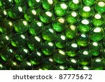 full frame abstract background picture with iridescent green glass beads in dark back - stock photo