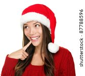 santa christmas woman looking to the side thinking happy and playful. Asian christmas girl wearing santa hat and red sweater isolated on white background. - stock photo
