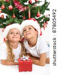 Smiling kids at christmas lazing in front of the decorated tree - stock photo