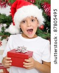 Happy surprised kid with christmas present in front of the decorated tree - stock photo