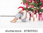 Happy little girl sitting under the christmas tree with presents - stock photo