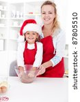 Woman and little girl preparing the christmas cookie dough together - stock photo