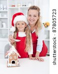 Woman and little girl making a gingerbread cookie house at christmas - stock photo
