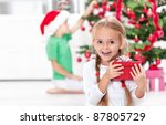 Childhood thrill of christmas - ecstatic little girl with present - stock photo