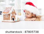 My christmas gingerbread cookie house - little girl in awe of her own work - stock photo